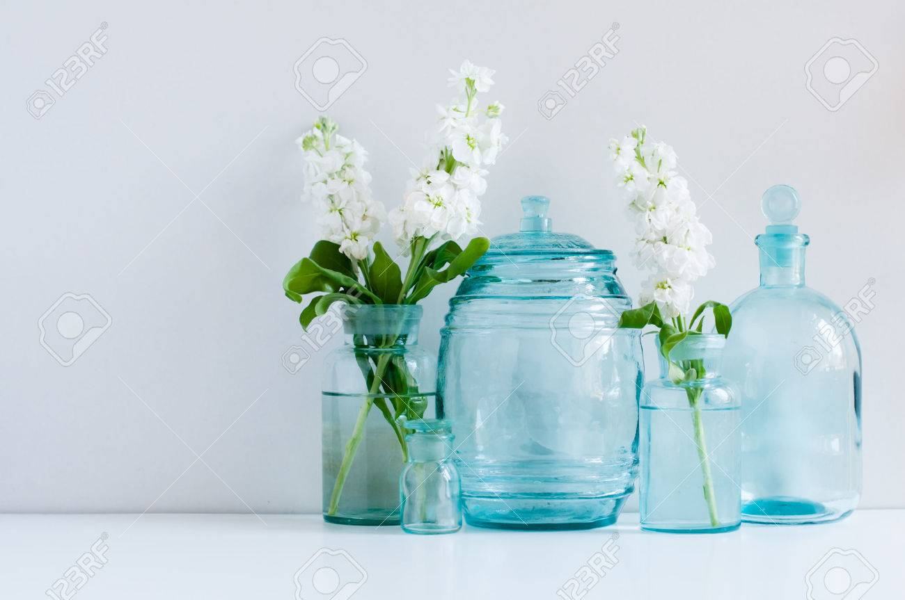 Vintage home decor background white matthiola flowers in vintage home decor background white matthiola flowers in different blue glass bottles vases and antique reviewsmspy