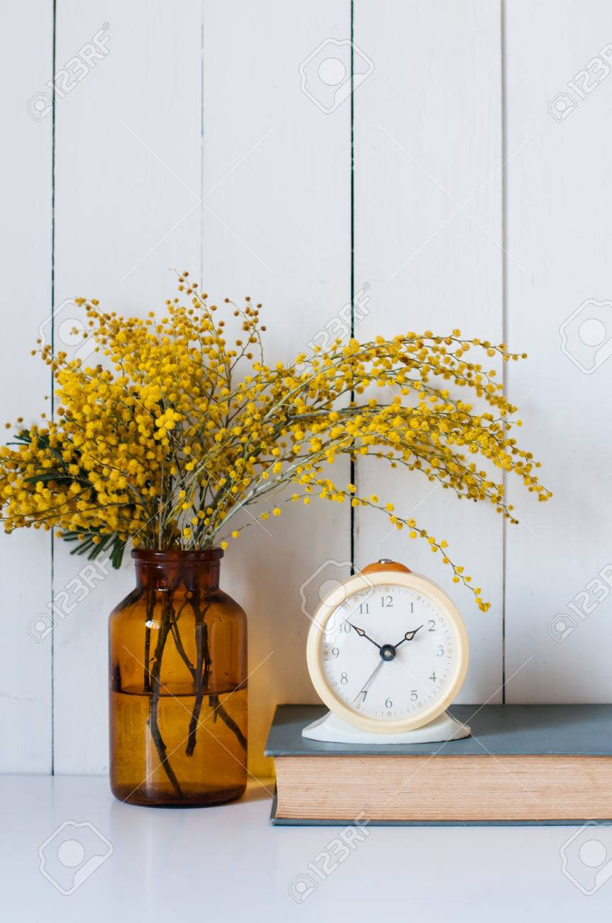 home decor photography. Home decor  mimosa yellow spring flowers in a vintage bottle book and alarm clock Decor Mimosa Yellow Spring Flowers In A Vintage Bottle