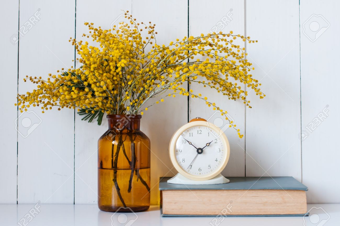 home decor mimosa yellow spring flowers in a vintage bottle home decor mimosa yellow spring flowers in a vintage bottle book and alarm clock
