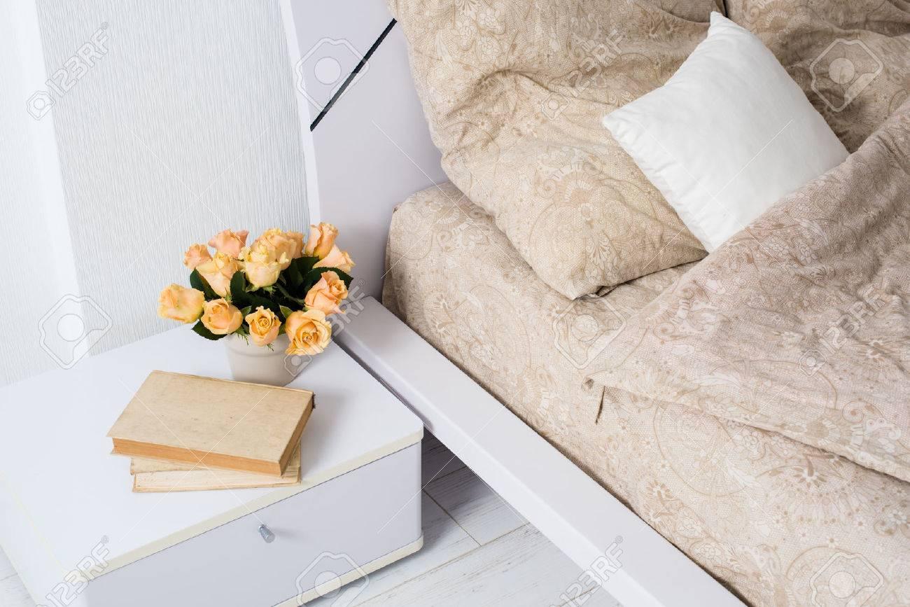 Ljust vit sovrum inredning, mysig säng med beige linne, blommor på ...