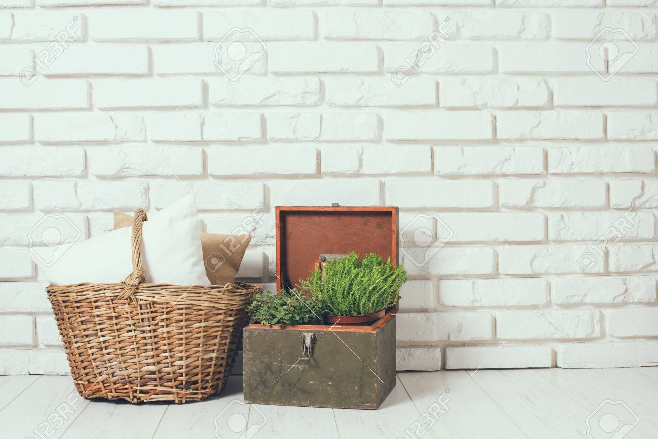 Wicker Basket With A Pillow And Green Home Plant At The White Brick Wall On