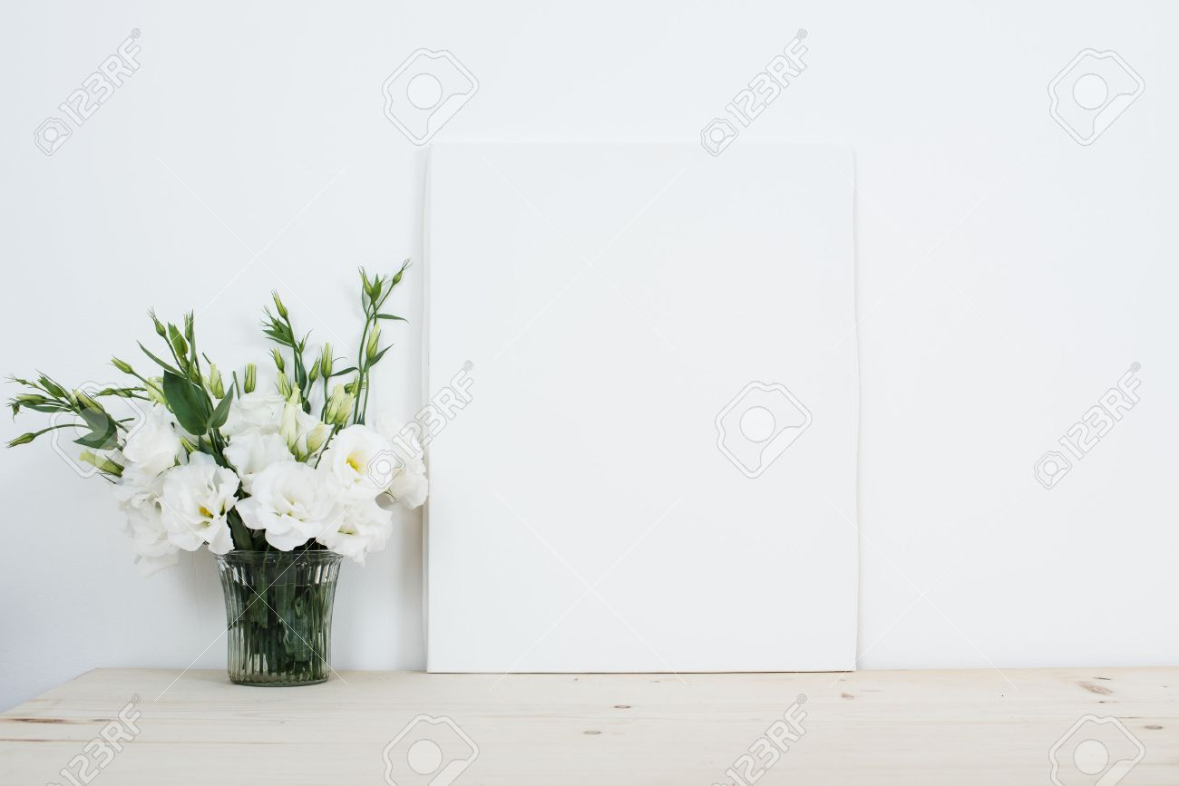 White interior decor fresh natural flowers in vase and empty white interior decor fresh natural flowers in vase and empty canvas on table stock photo reviewsmspy