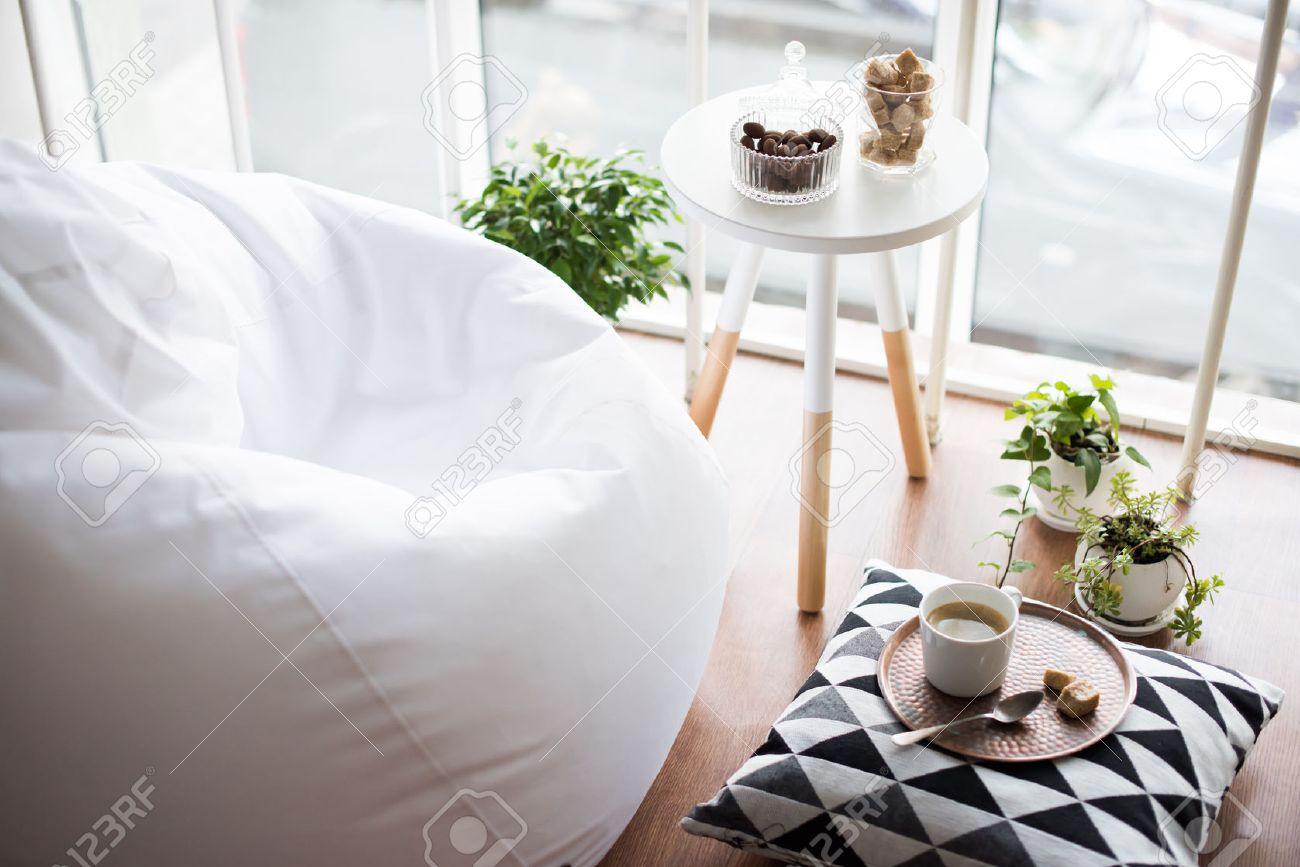 Coffee served on table in bright light scandinavian style hipster interior, cozy loft room with large windows closeup - 63775612