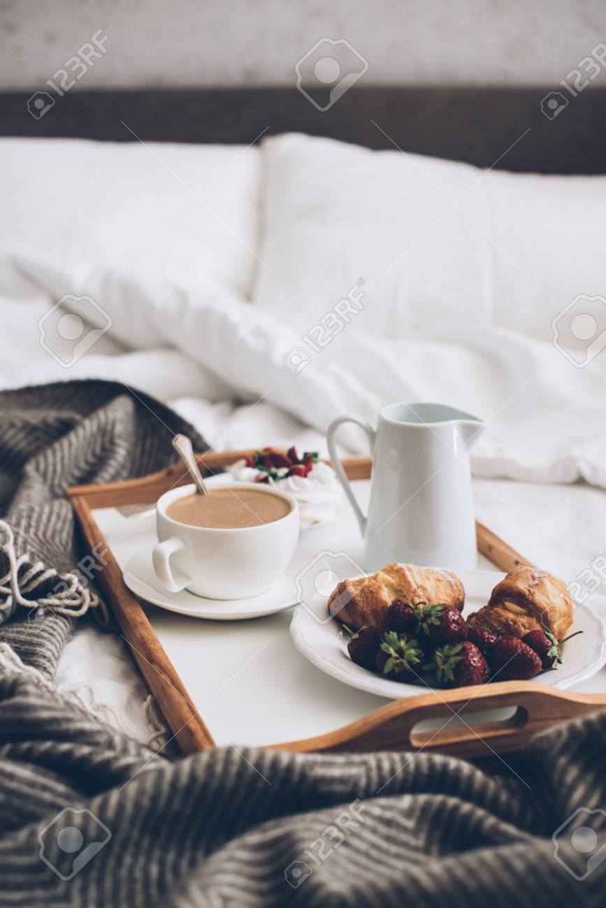 Traditional romantic breakfast in bed in white and beige bedroom