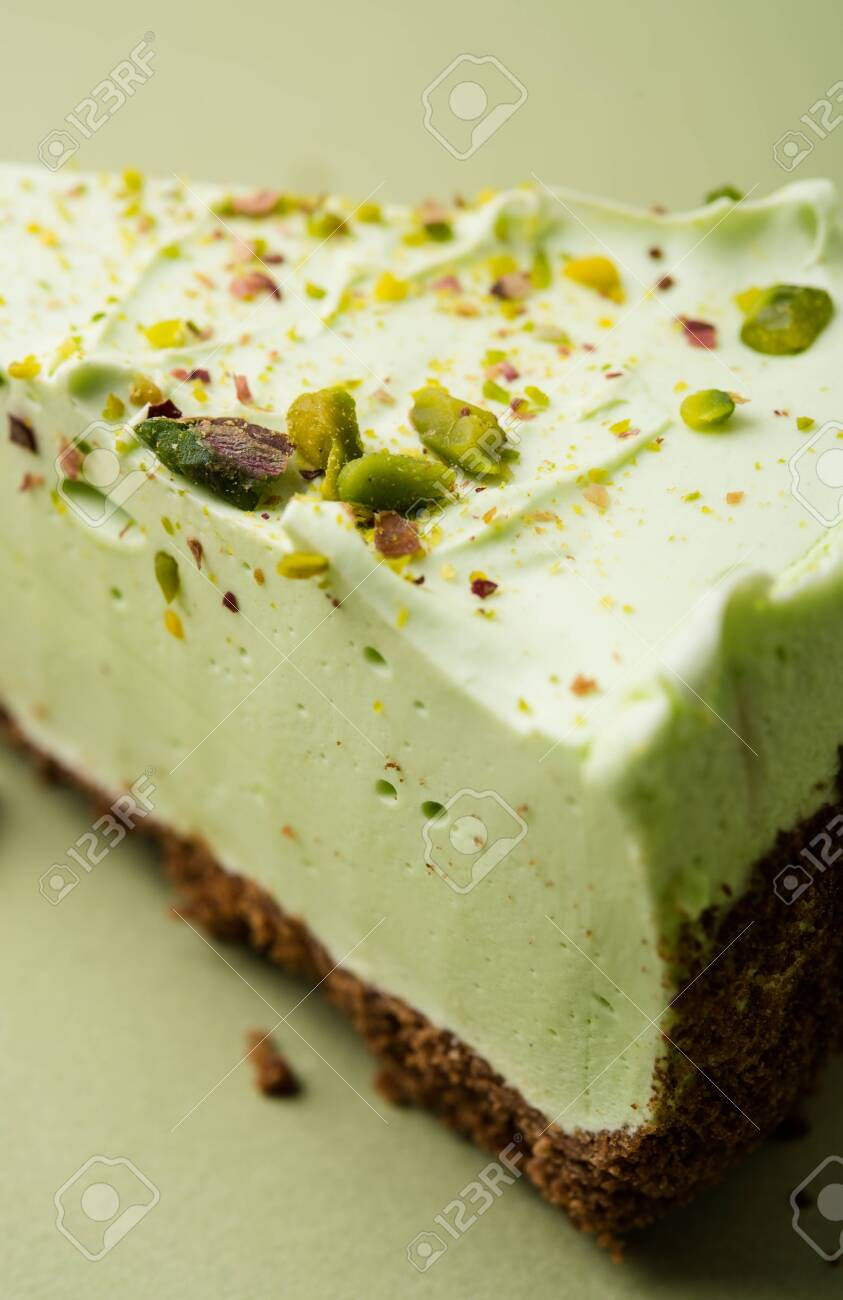 One slice of pistachio cheesecake on sight green background - 129813602