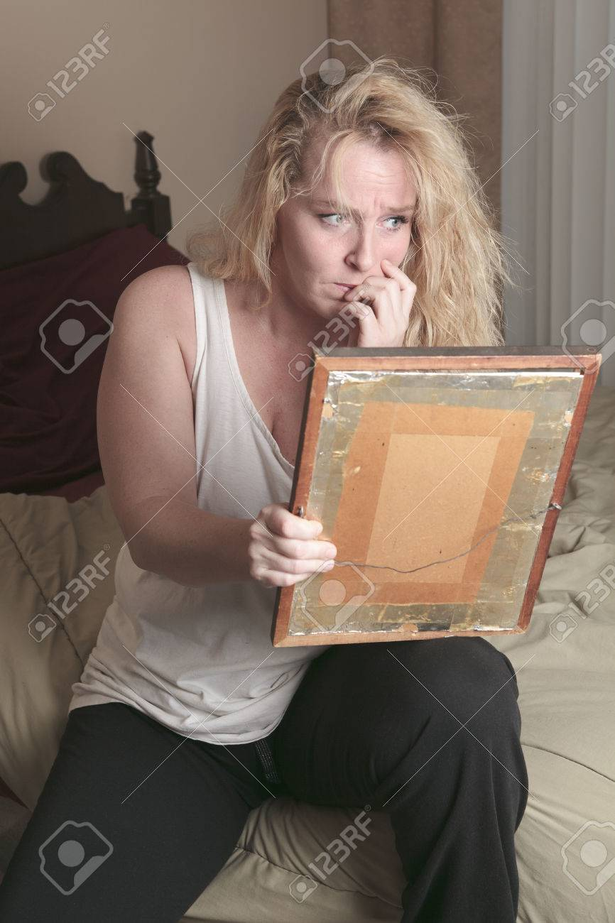 A sad woman take a look on picture frame - 36919383