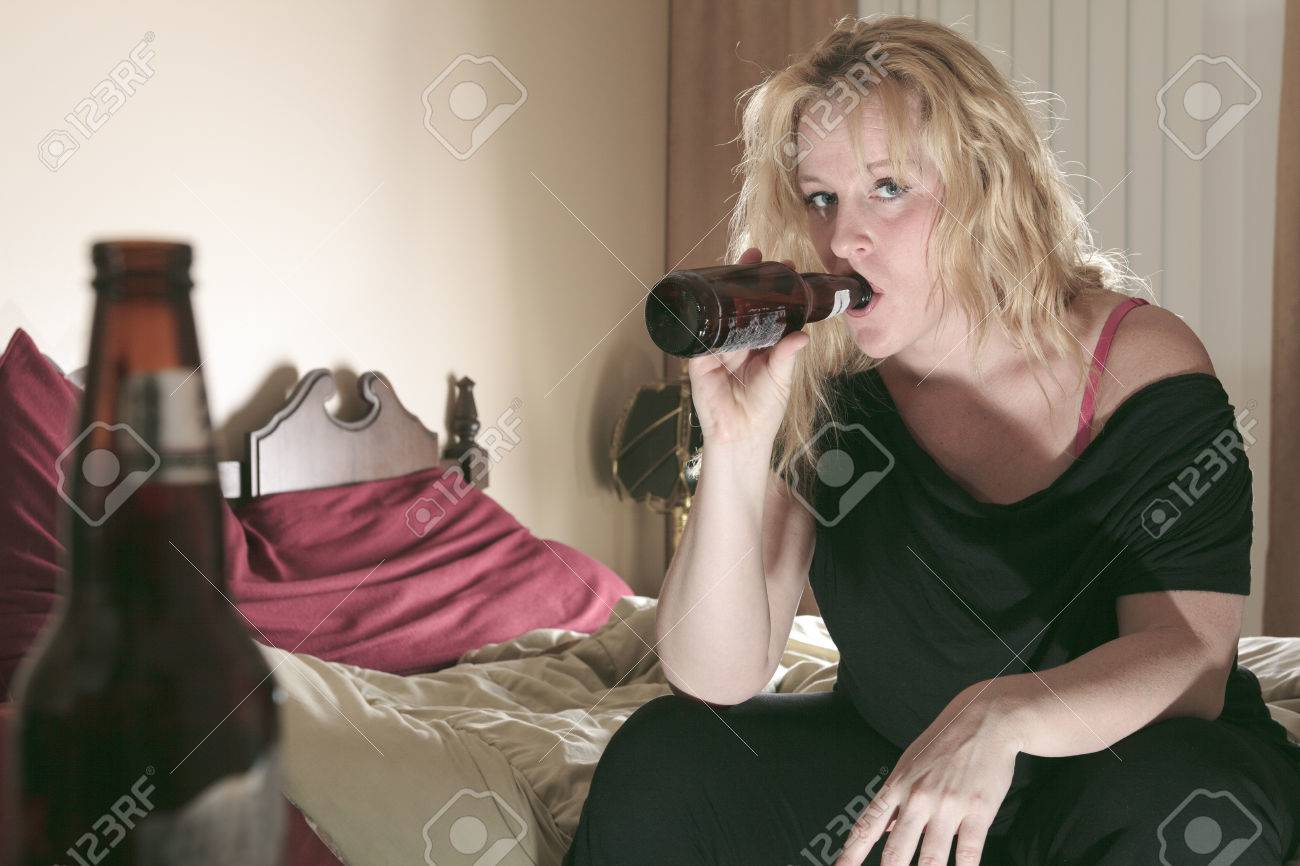 A alcoholic woman drinking beer in his bedroom. - 36919354