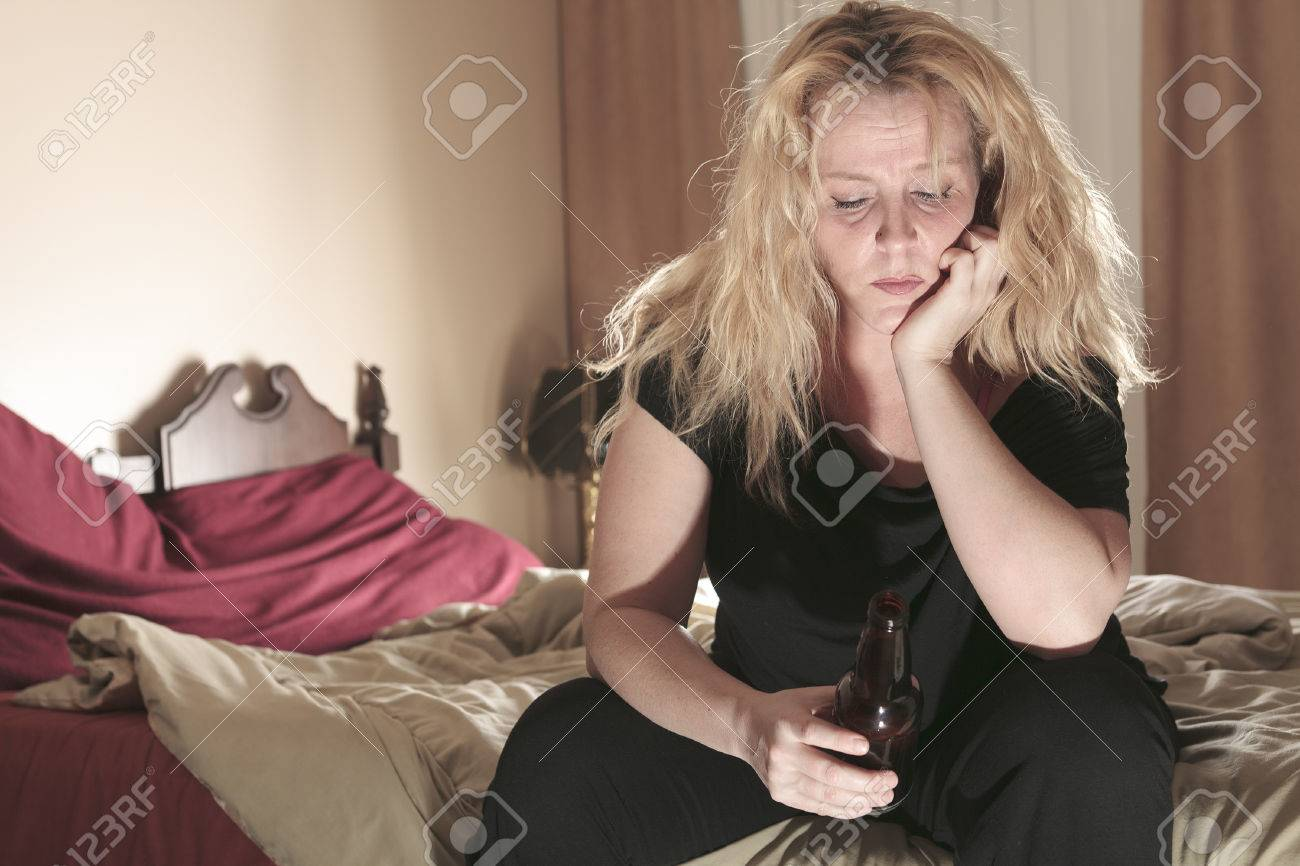 A alcoholic woman drinking beer in his bedroom. - 36919360
