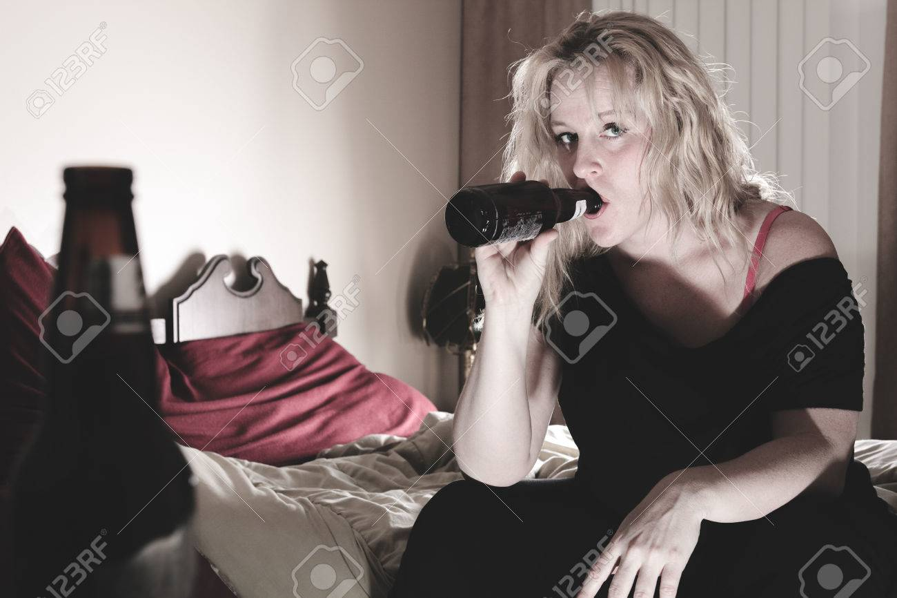 A alcoholic woman drinking beer in his bedroom. - 42930685