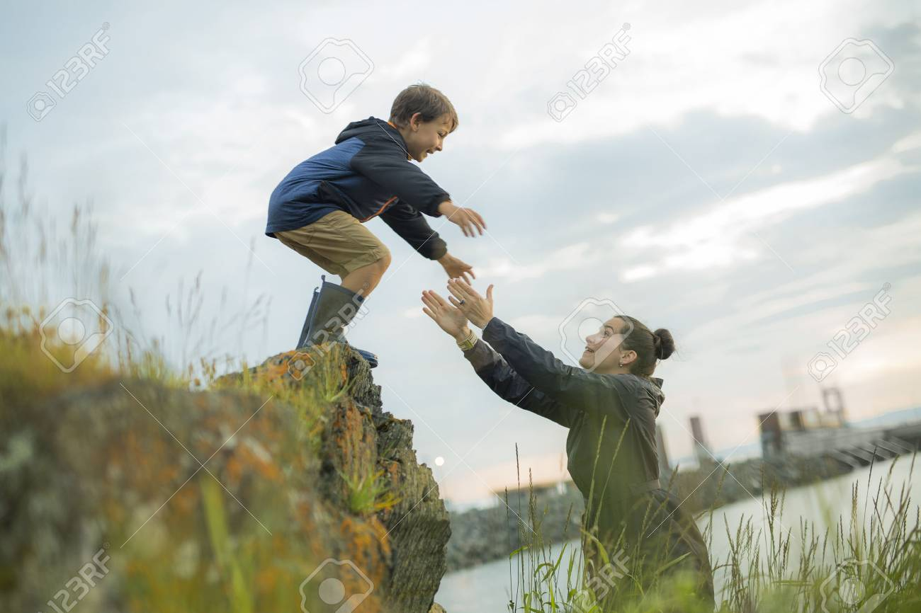 A mother Helping Children To Jump Off Rocks - 61116909
