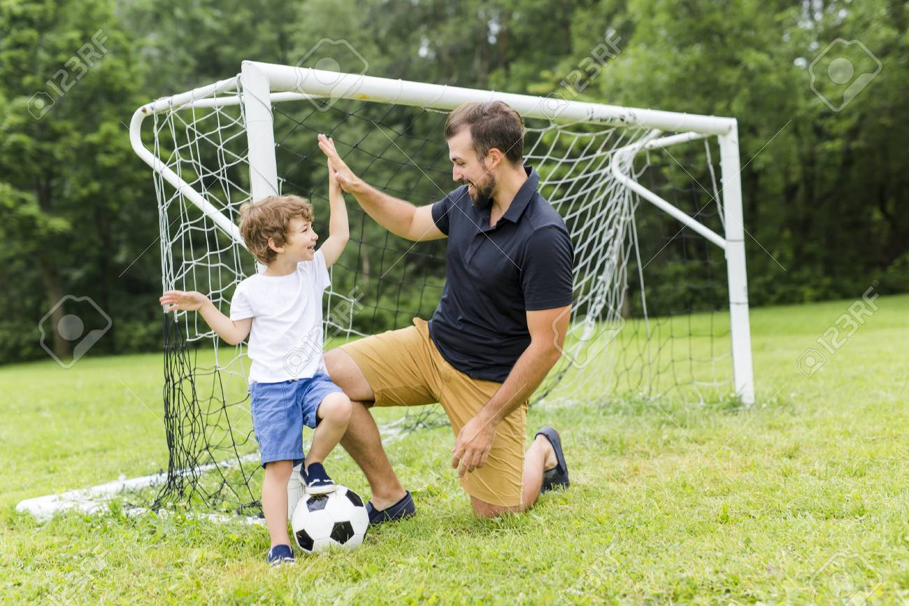 father with son playing football on football pitch - 85213592