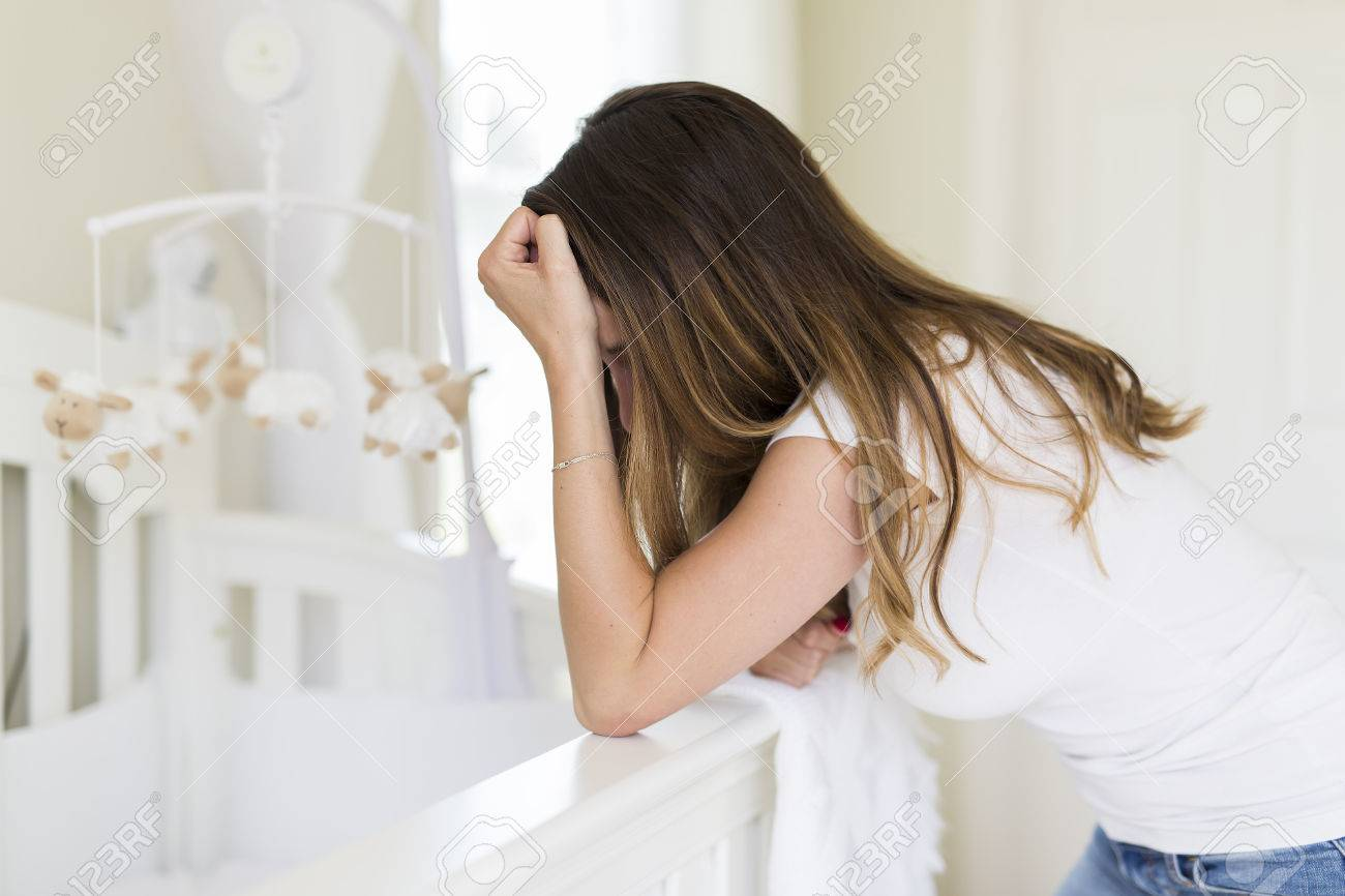 Depressed young woman in baby room - 85493583