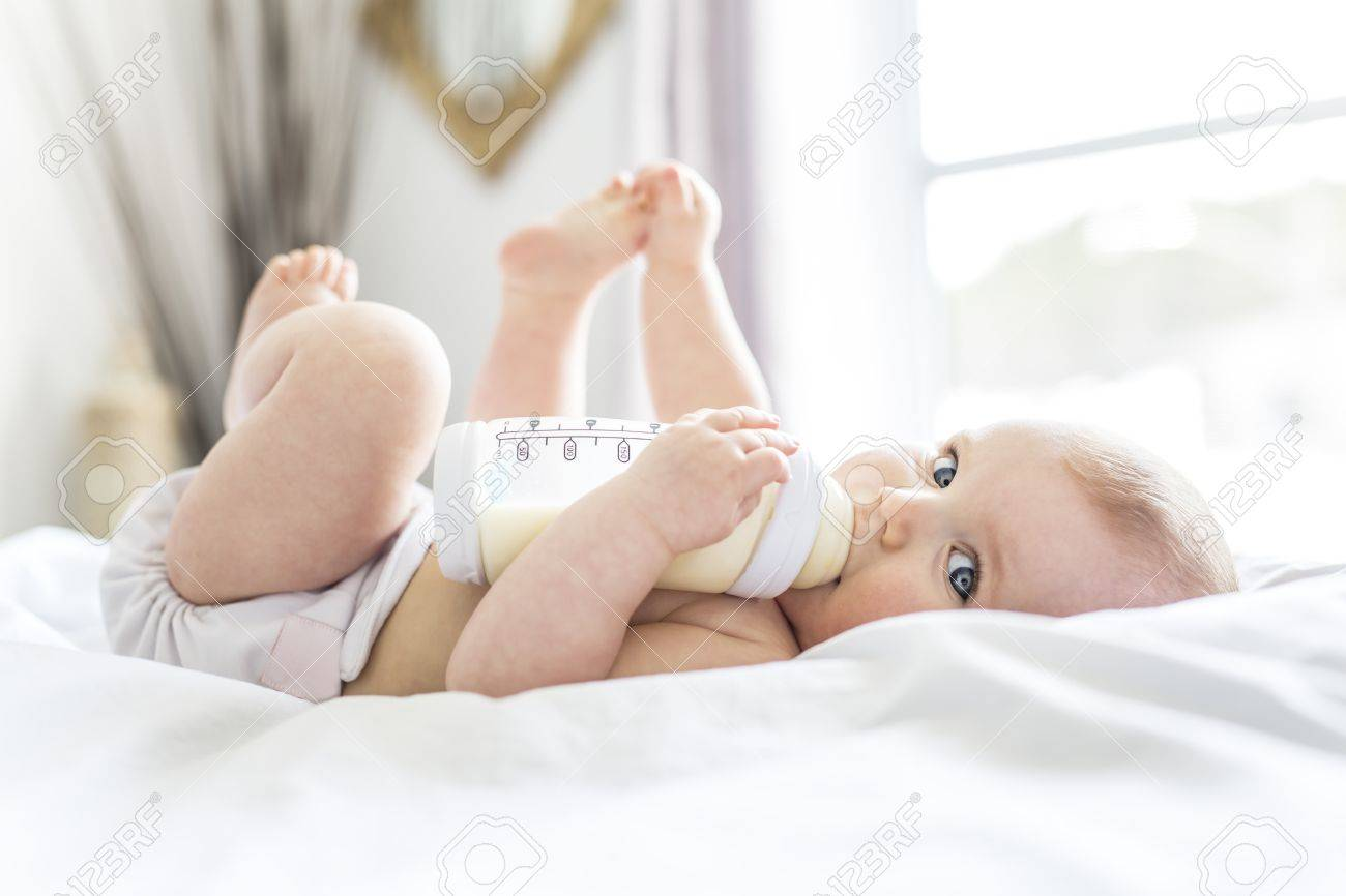 Pretty baby girl drinks water from bottle lying on bed. Child weared diaper in nursery room. - 86435836