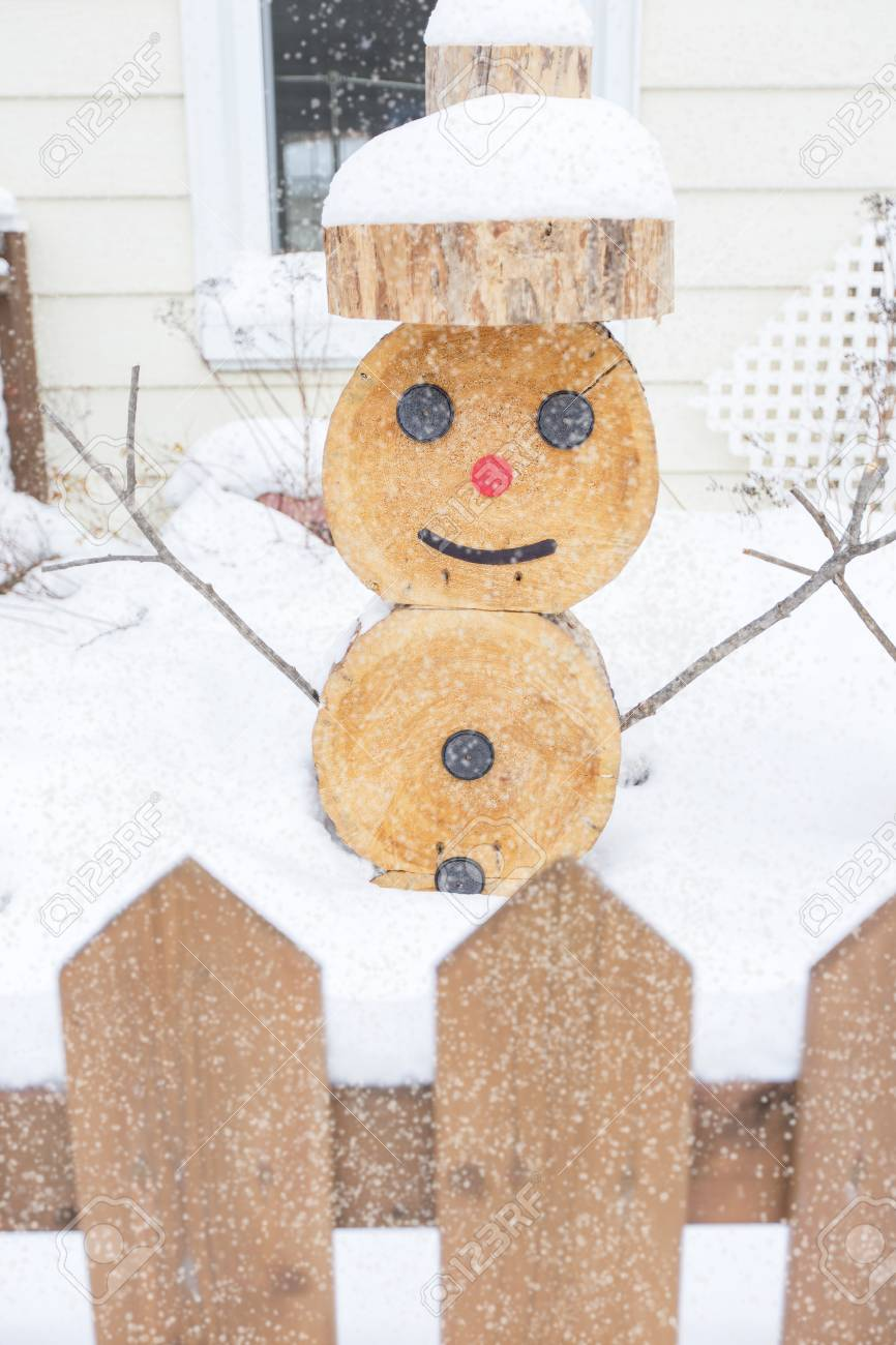 a snowman made in piece of wood with fence on the front stock photo 86686203