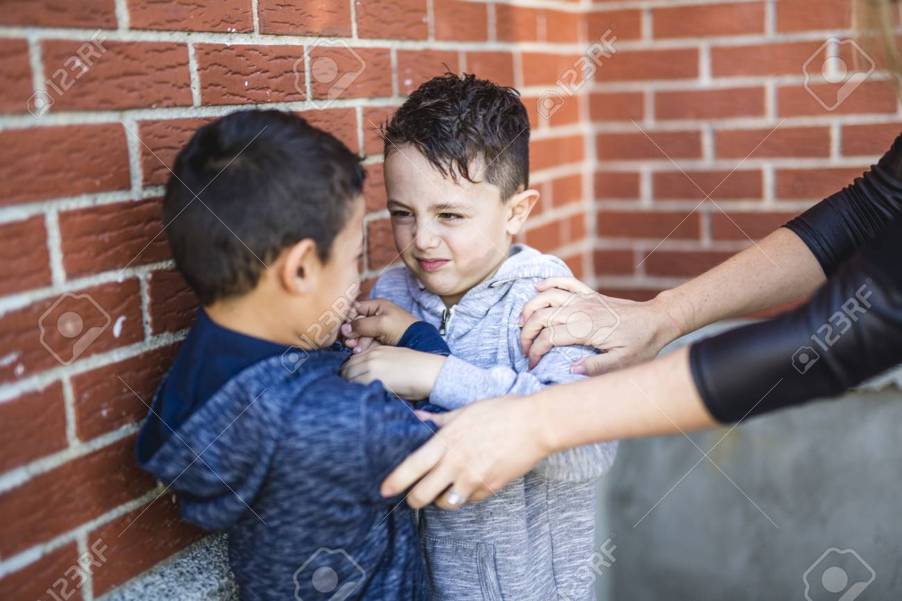 Teacher Stopping Two Boys Fighting In Playground - 86942541