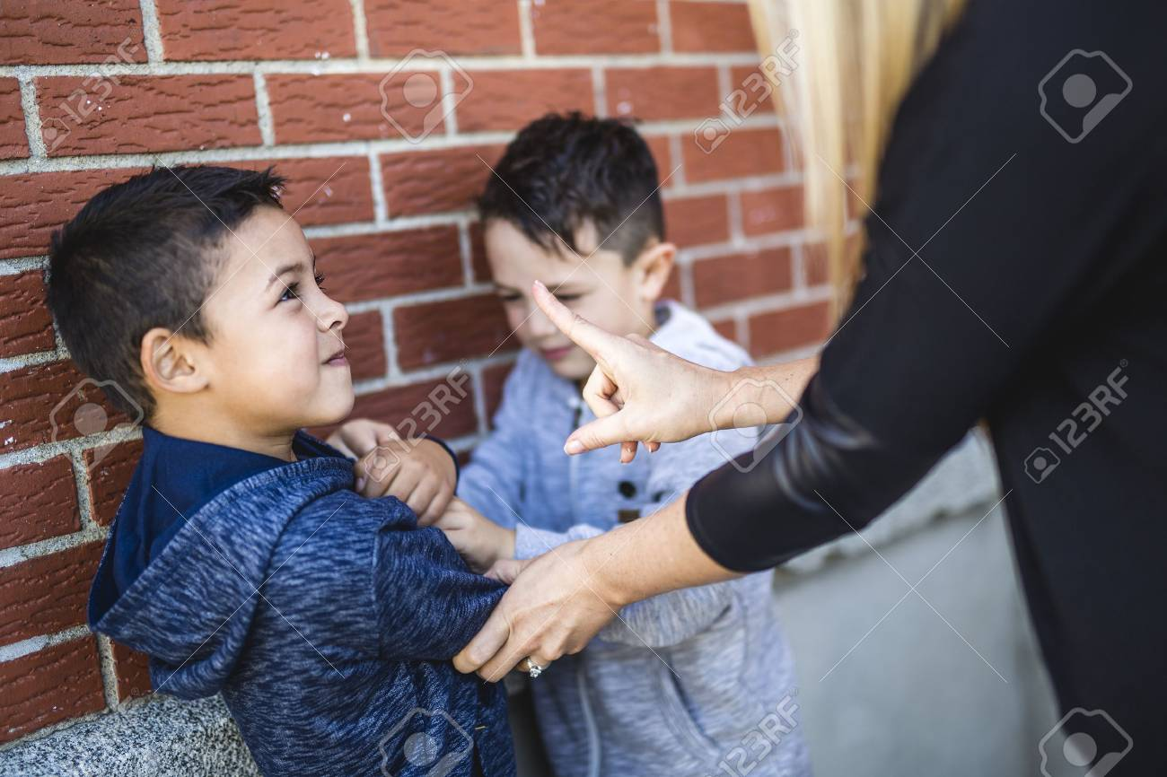 Teacher Stopping Two Boys Fighting In Playground - 86942542