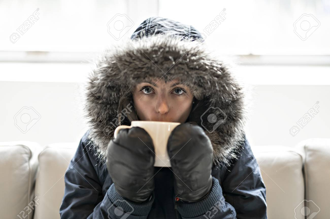 Woman have cold drink coffee on the sofa at home with winter coat - 112330875