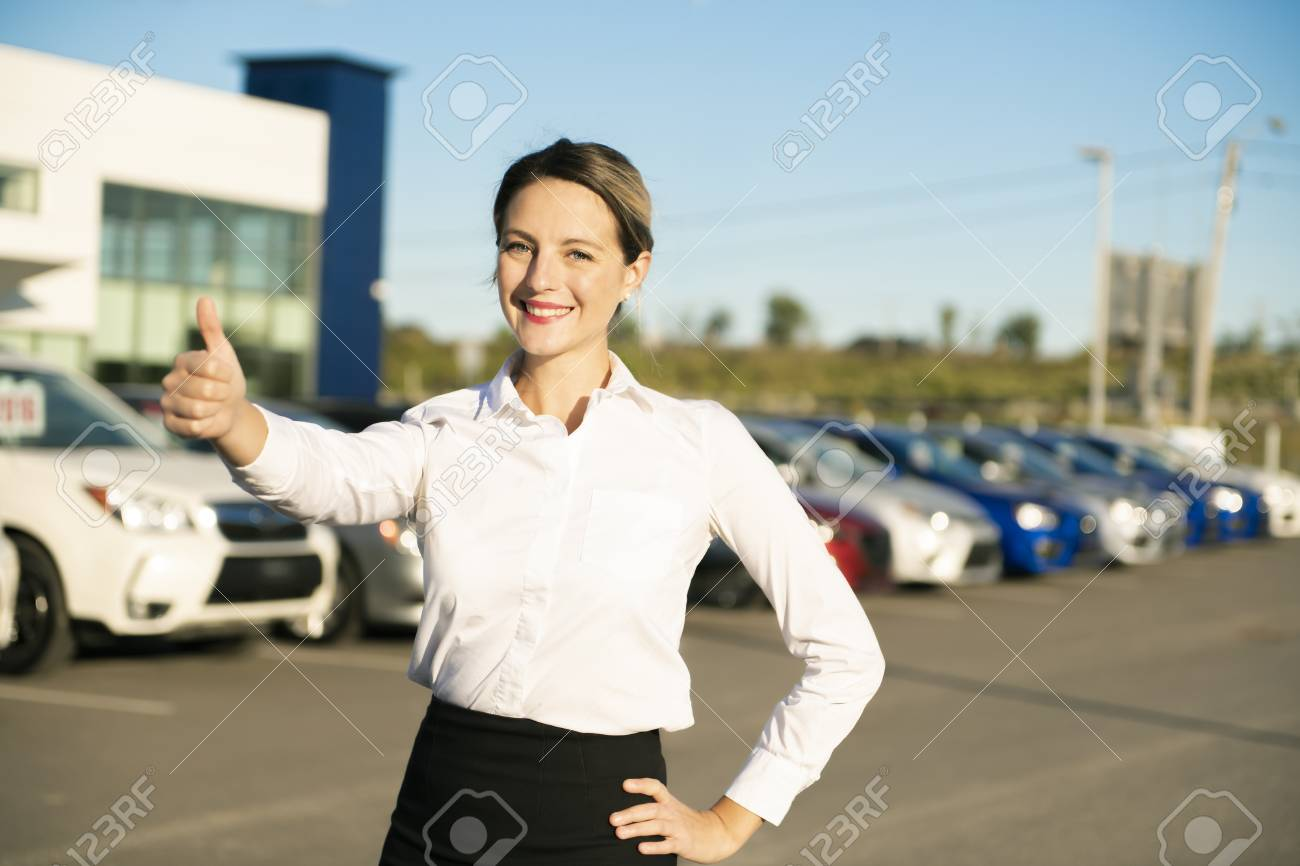 Young Woman Car Rental In Front Of Garage With Cars On The Background