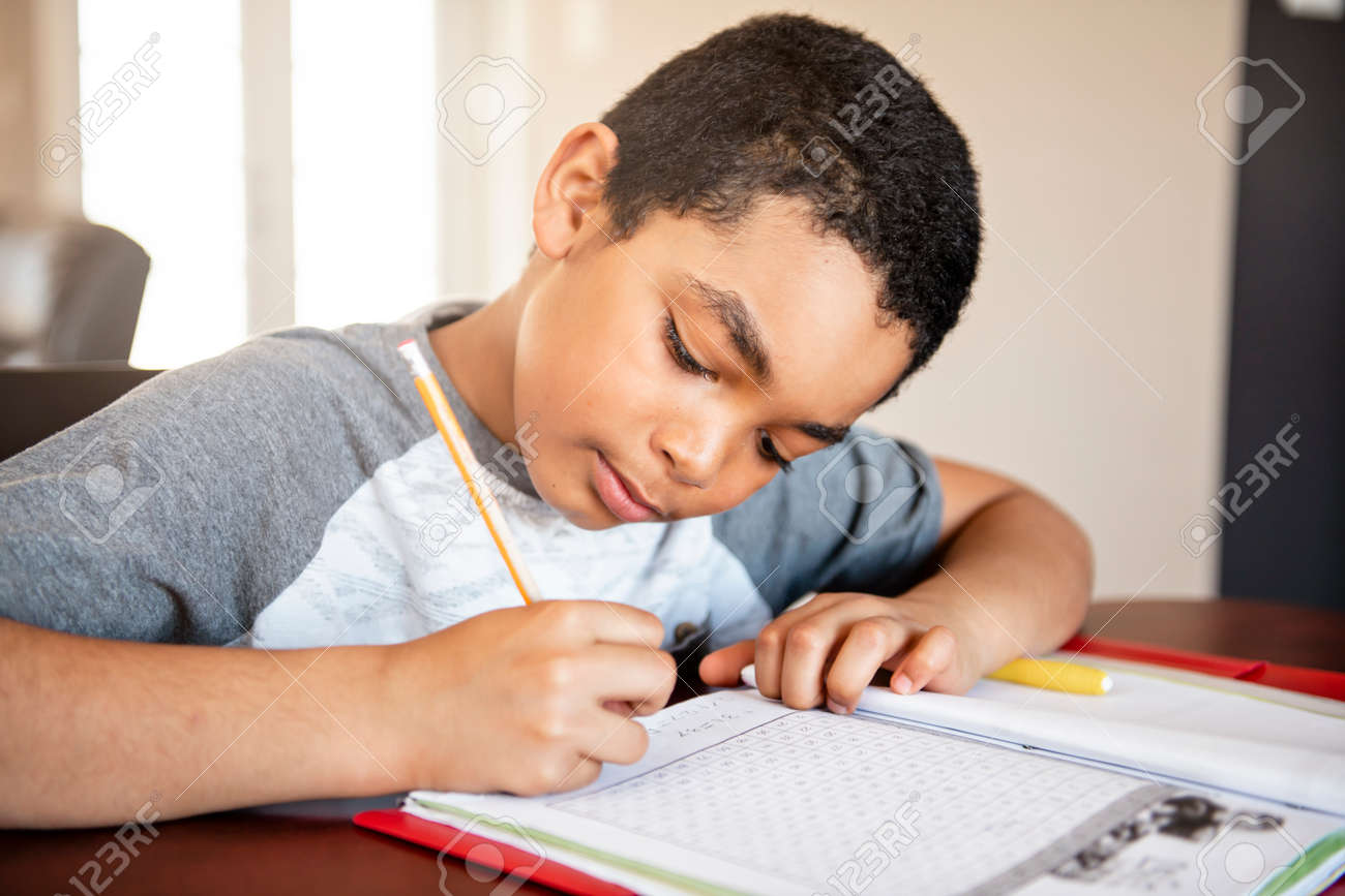 A male black child doing homework at home - 158125668