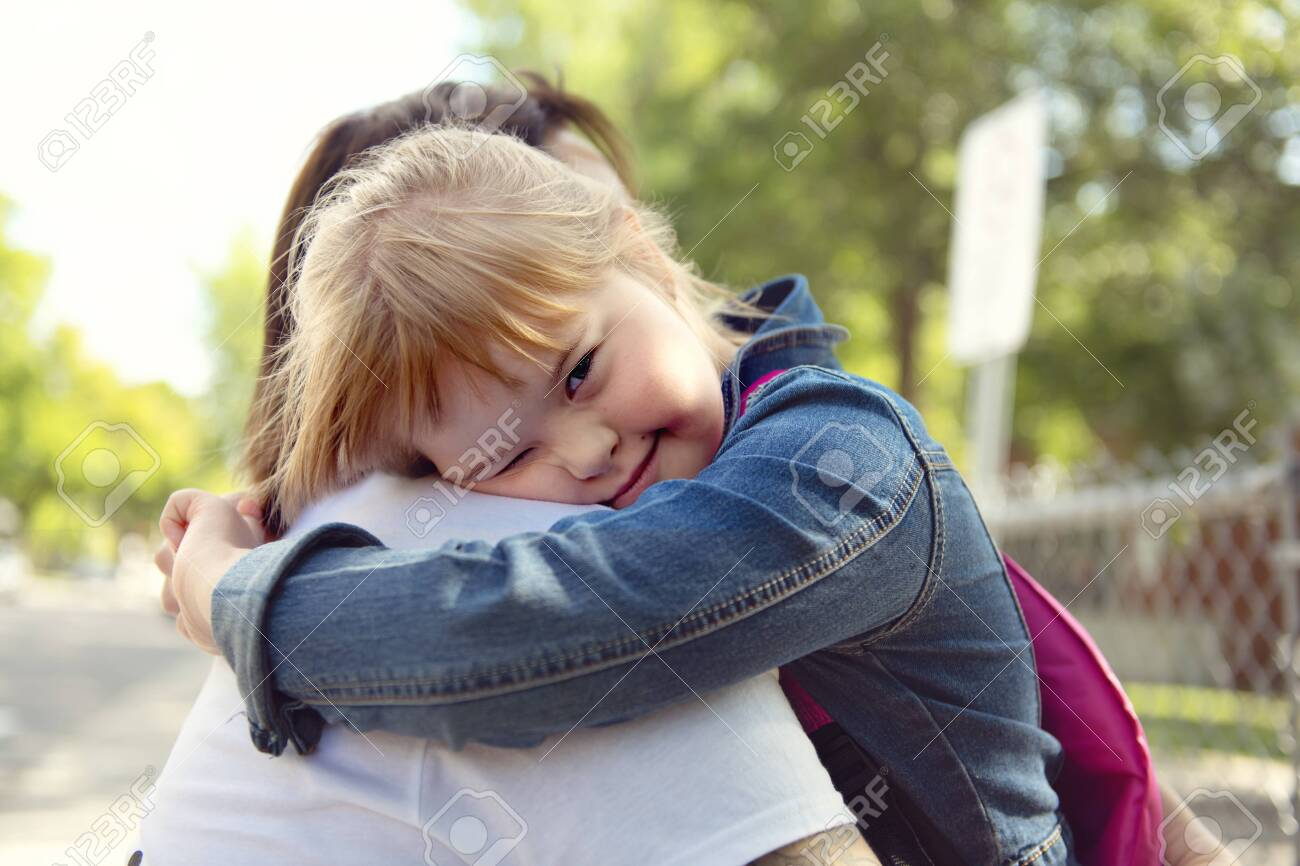 A portrait of trisomie 21 child girl outside hugging his mother on a school playground - 158154961
