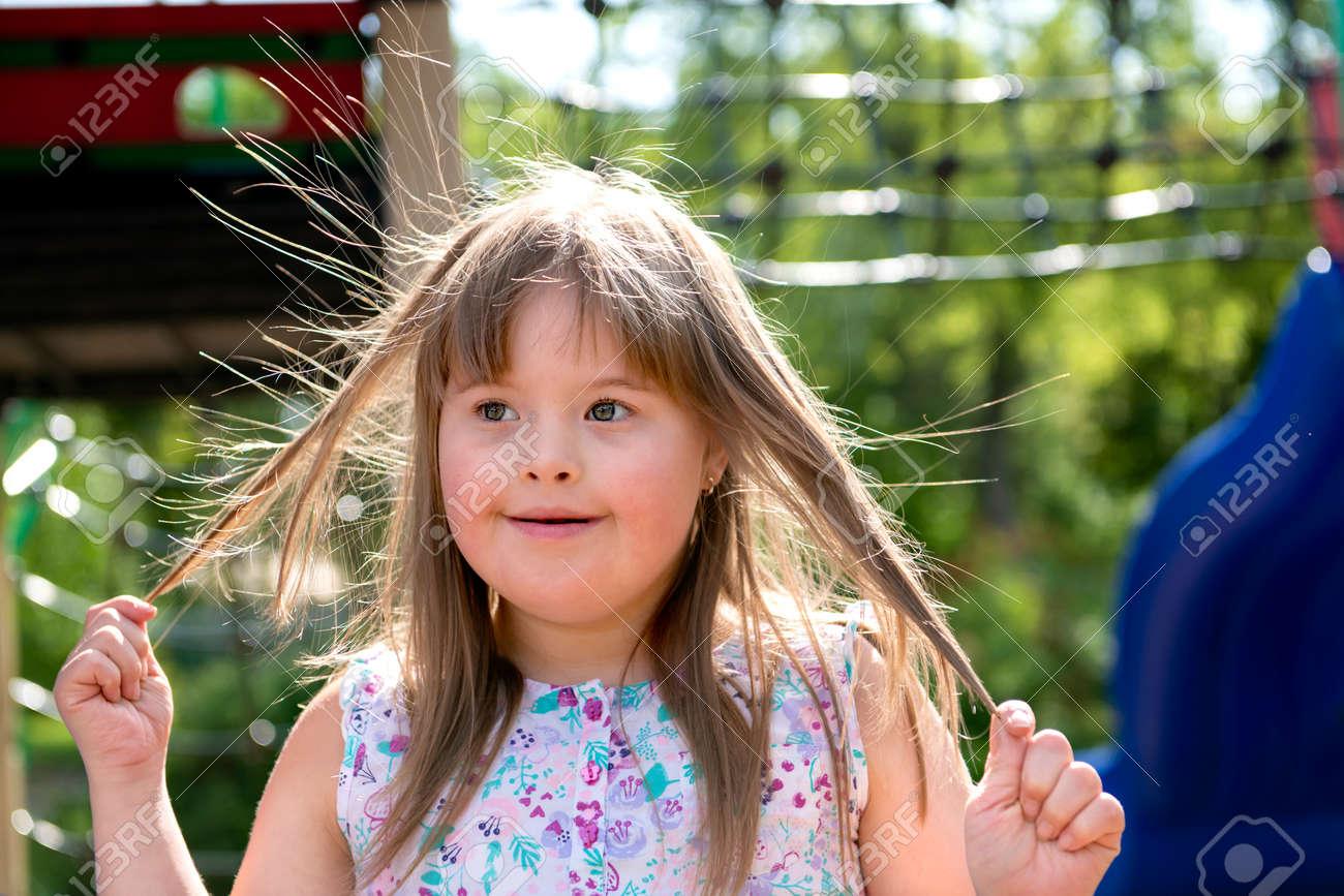 A portrait of trisomie 21 child girl outside having fun on a park - 158155386