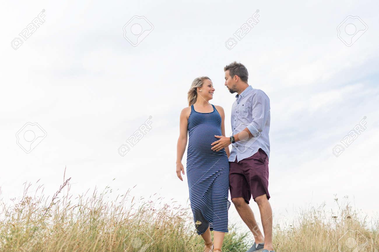 pregnant woman at beach with husband having fun - 158345071