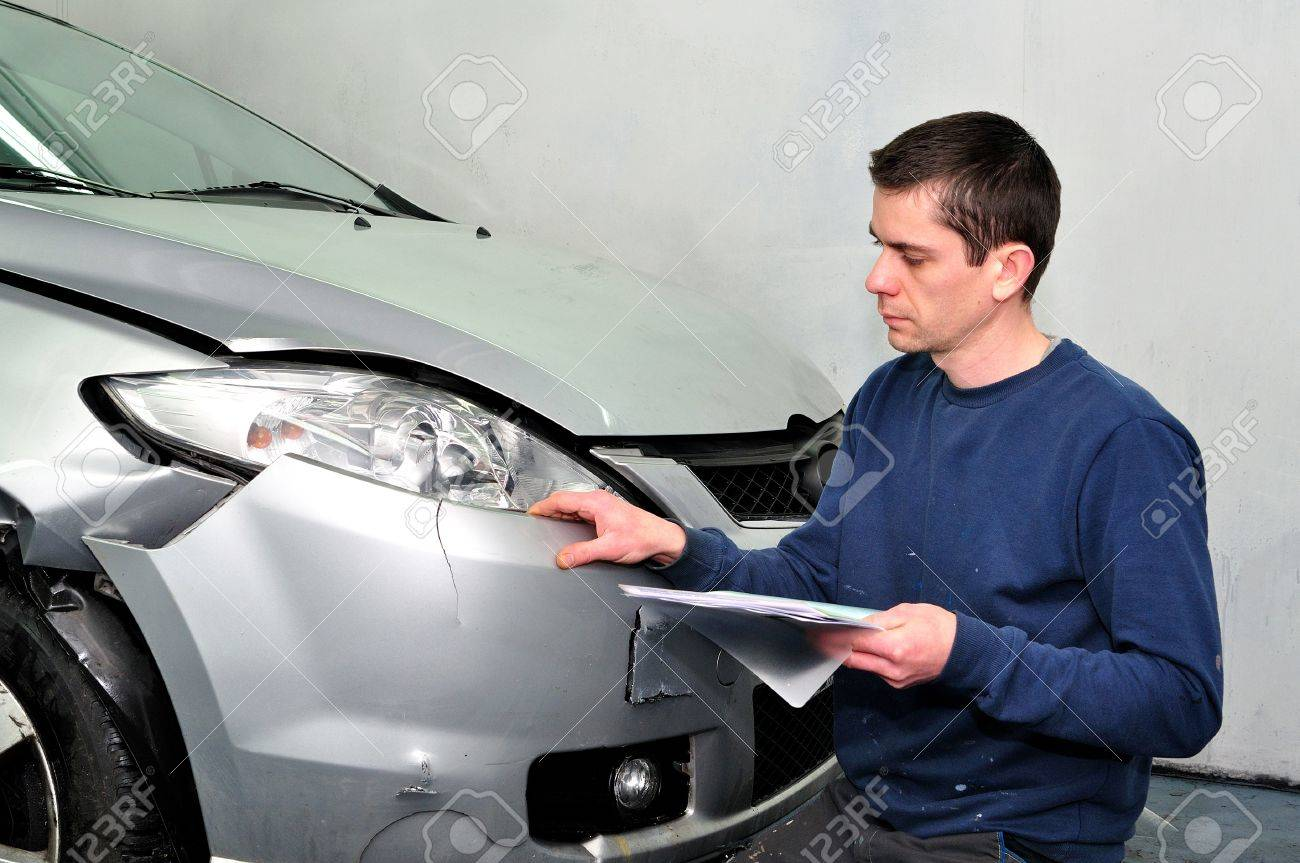 Insurance expert examining car damage Stock Photo - 17701219