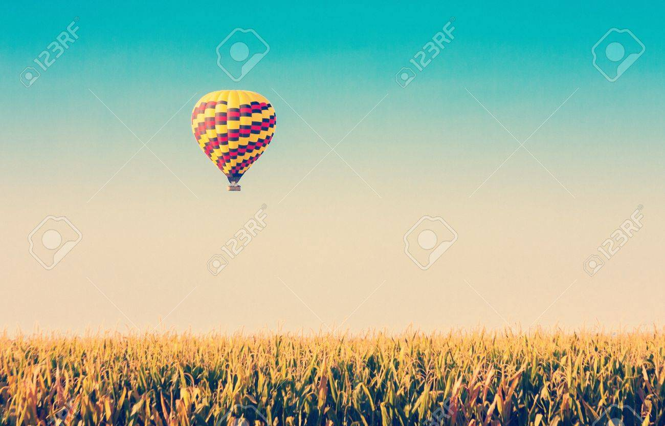 Hot air balloon flying over corn fields against blue sky in old style - 21167026