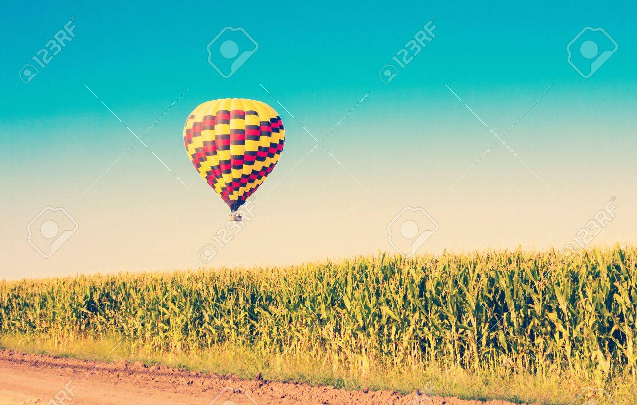 Hot air balloon flying over corn fields against blue sky in old style - 21167027
