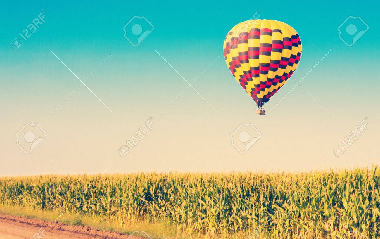 Hot air balloon flying over corn fields against blue sky in old style - 21167028