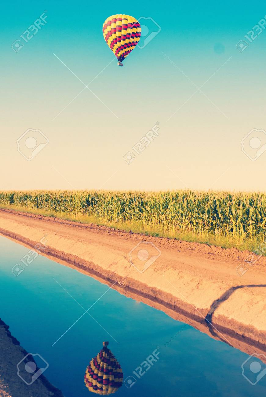 Hot air balloon flying over corn fields against blue sky in old style - 21167030