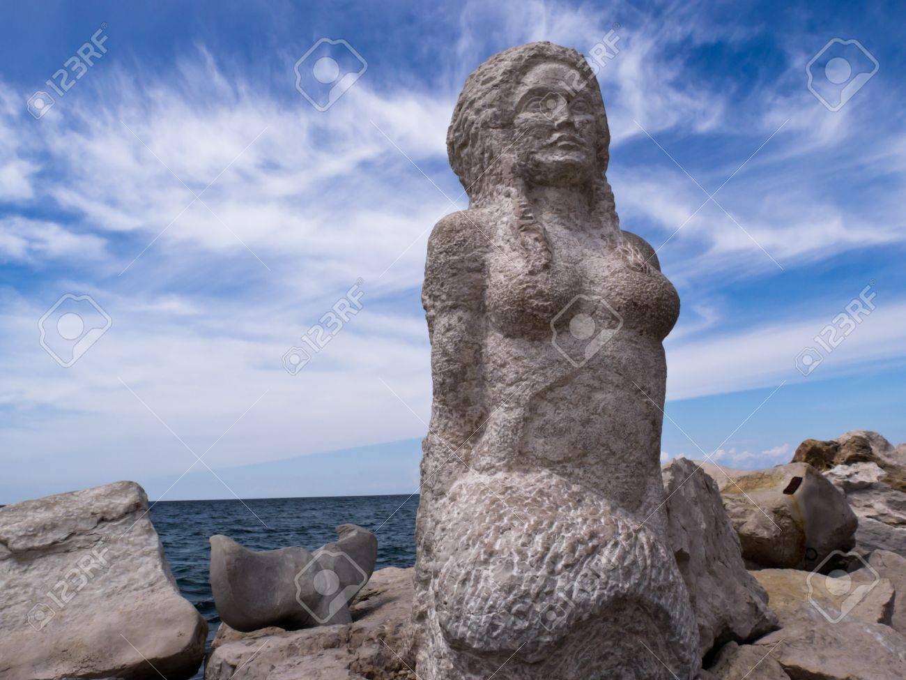 a mermaid sculpture carved from stone a rocky background the