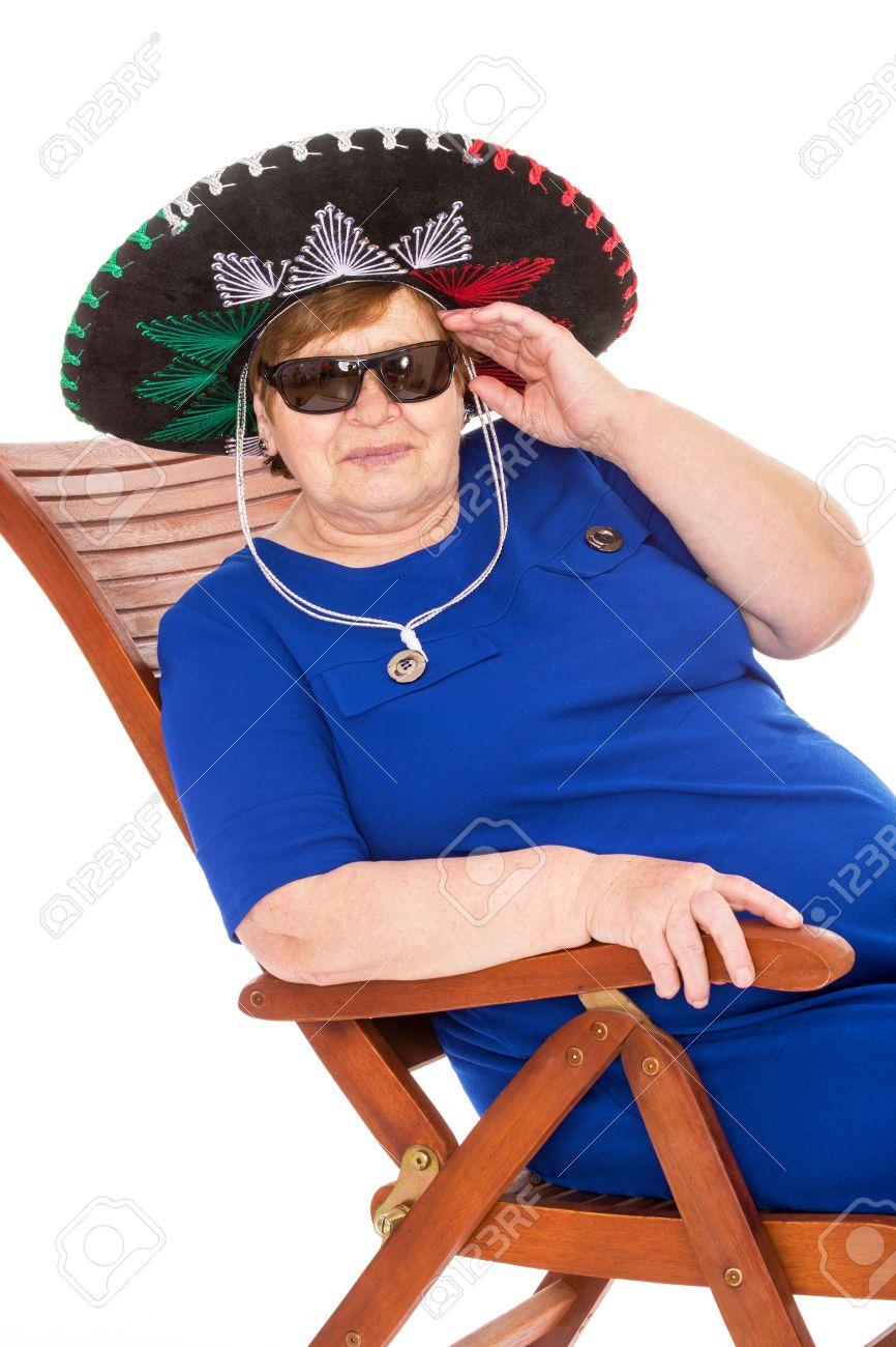 Vieille Femme avec chapeau et lunettes de soleil assis sur