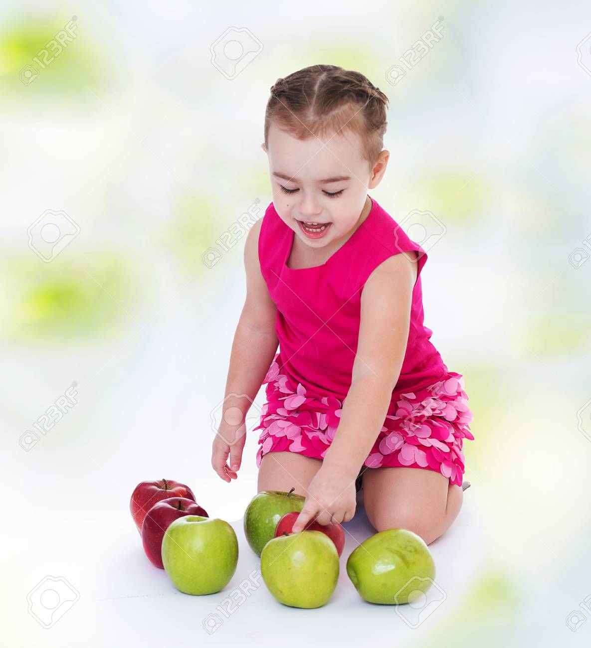 4eb093b3e3a Charming little girl in a red dress pointing at a green apple.Concept of  childhood