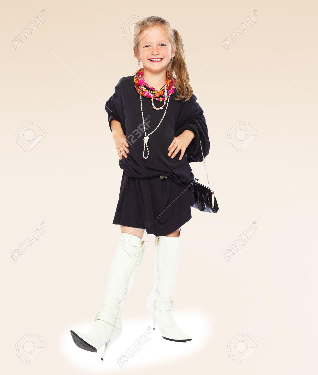 Niña De Moda Con Un Vestido Negro Y Botas Largas De Alta Suela