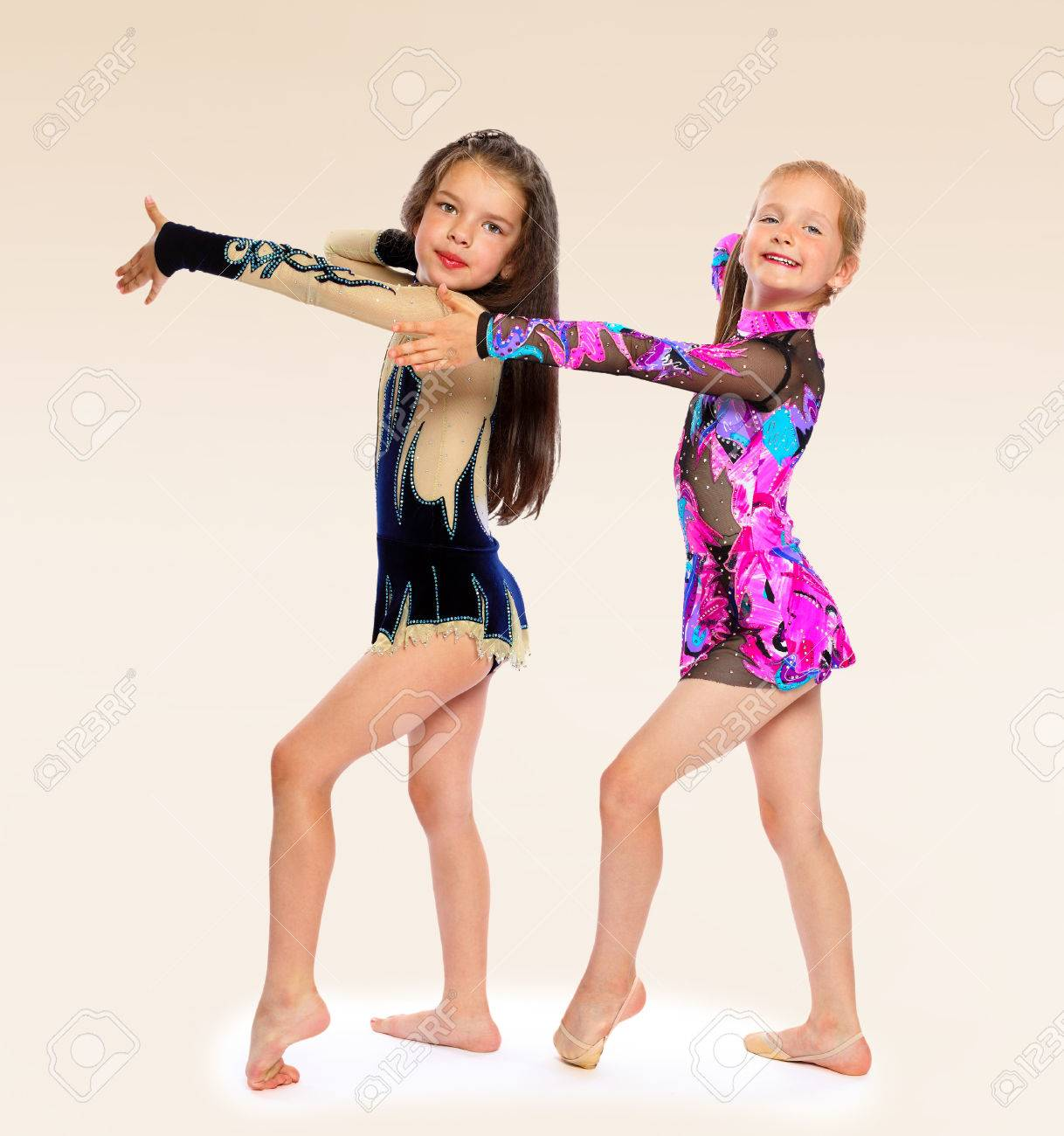 Two little beautiful girls gymnasts perform sport exercises