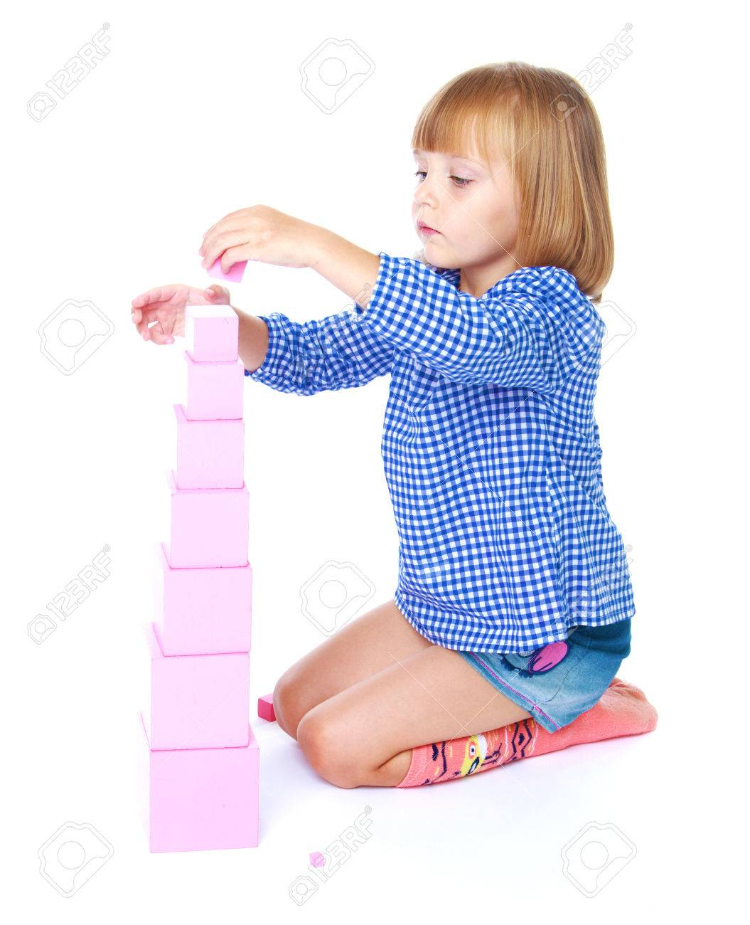 charming little girl collects in the Montessori classroom pyramid isolated on a white horse - 34543604