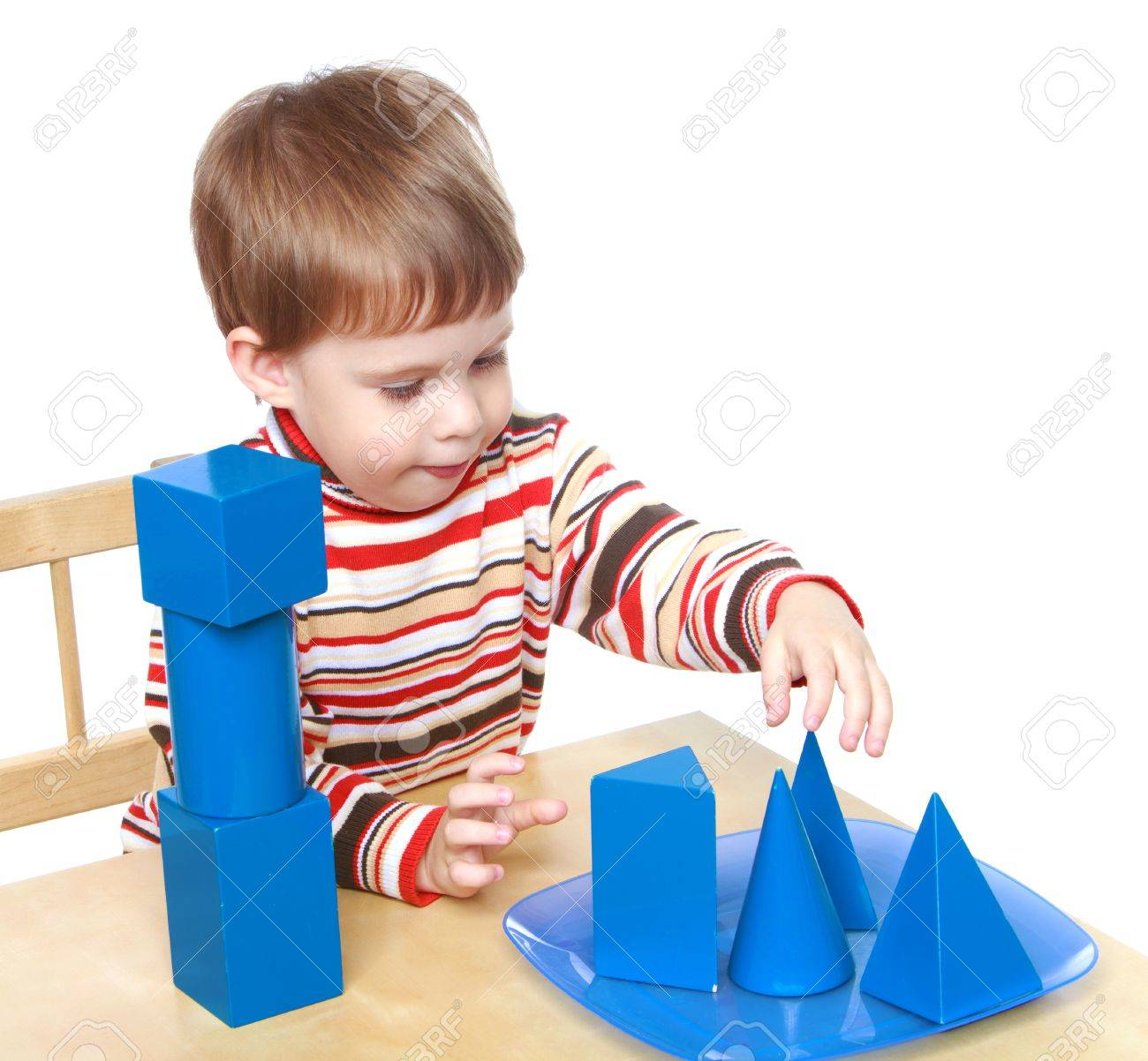Little boy plays cubes and cones sitting at the table, Montessori kindergarten.Isolated on white background, Lotus Childrens Center. - 36176019