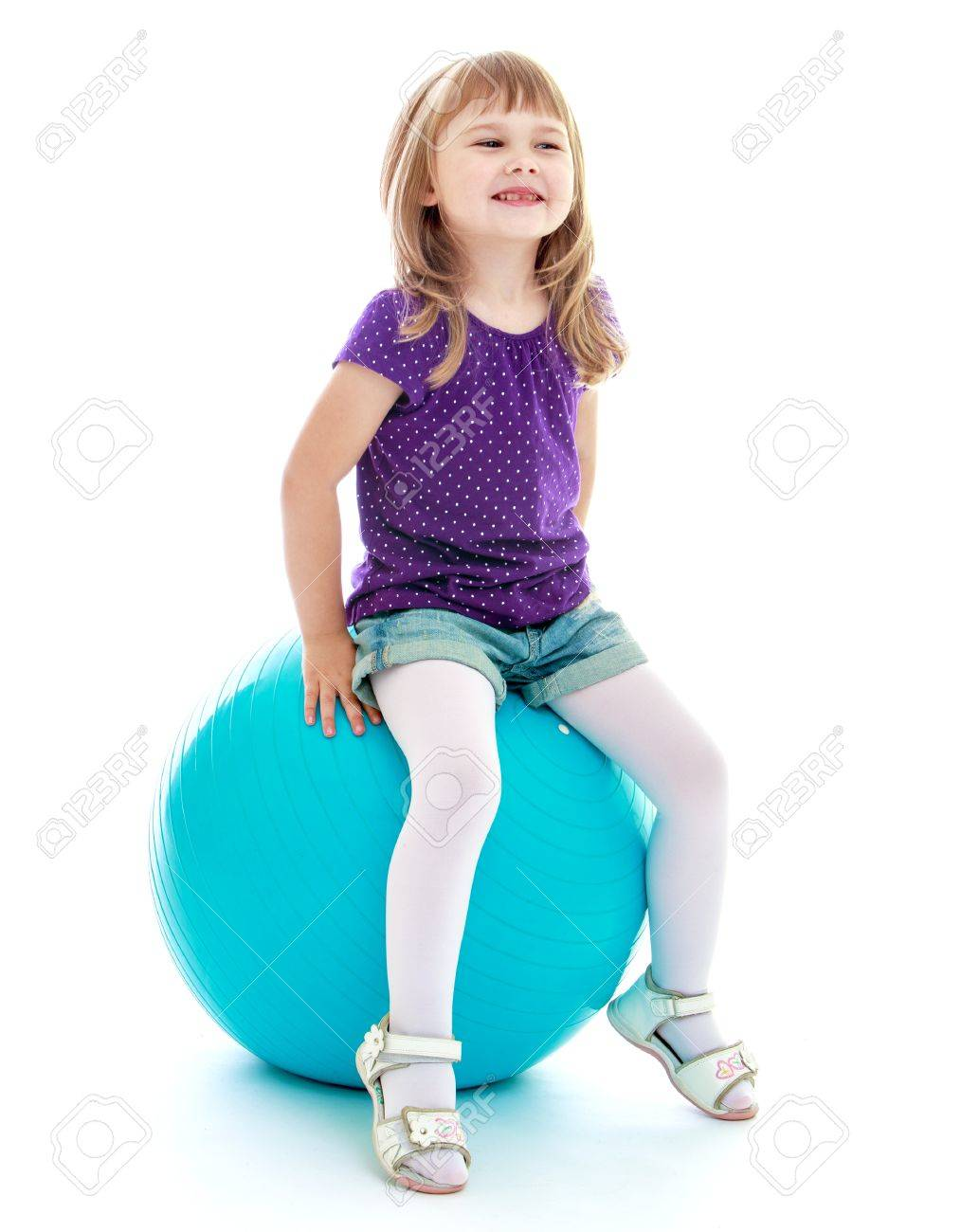 Little girl in short shorts sitting on the big blue linen.Isolated on white. - 36508711