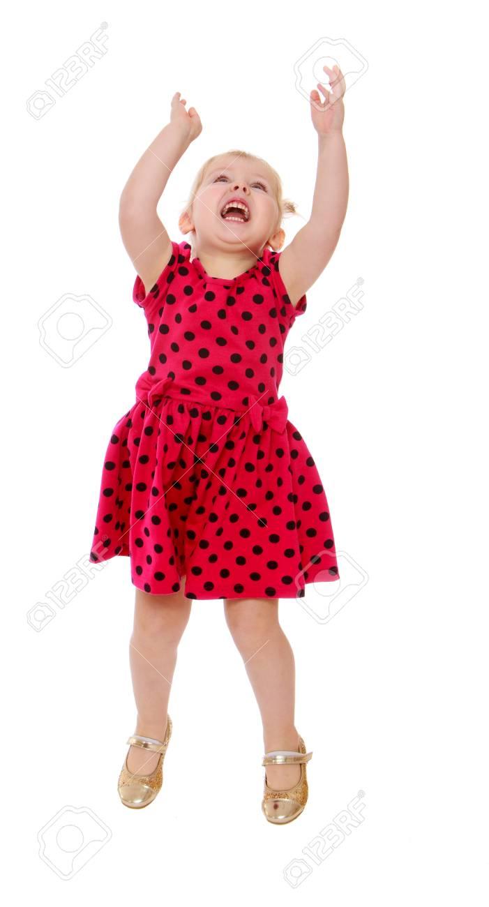 Niña Rubia Con Un Vestido De Lunares Rojos Salta Con Los Brazos En Alto Aislado En Fondo Blanco