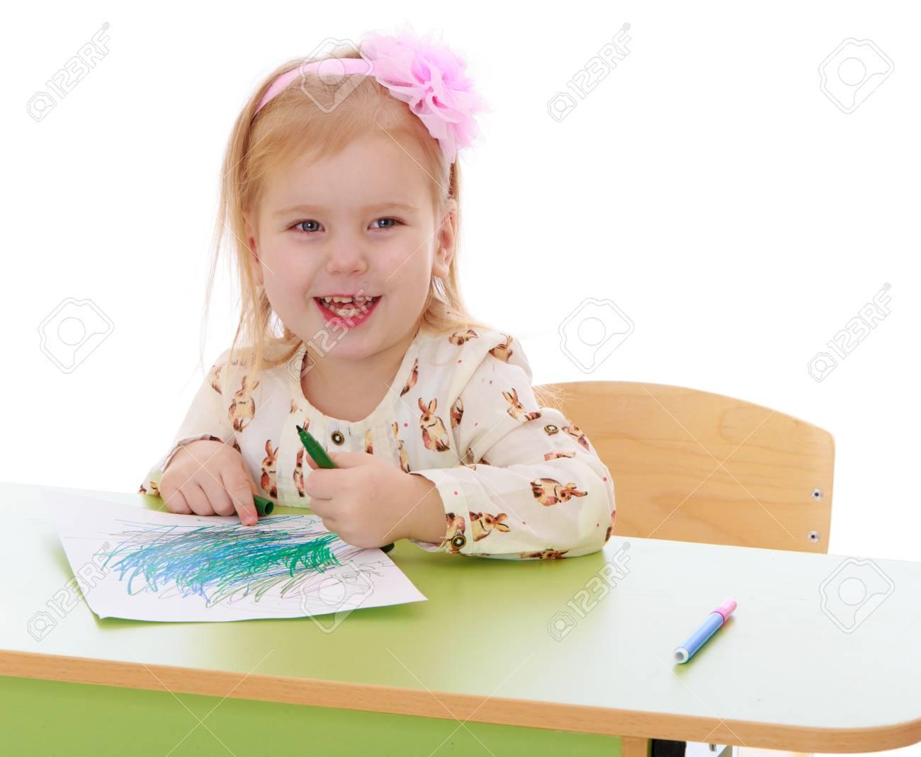 7ad32af2e4 Foto de archivo - Niña rubia caucásica dibuja con lápices sentado en la  mesa