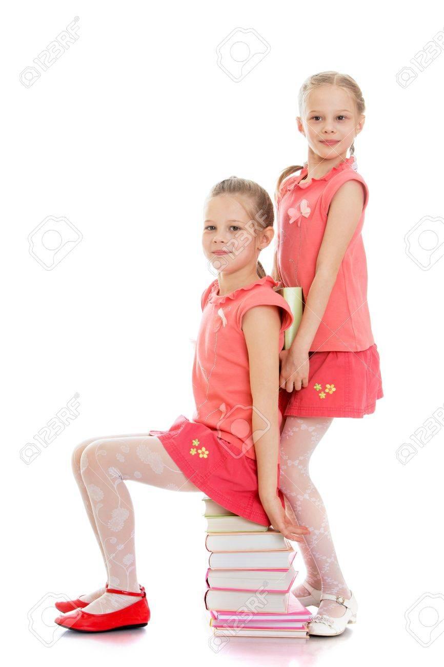 c2b0956d56 Foto de archivo - Hermanas niñas diversión niñas en faldas cortas de color  rosa que se divierten sentado sobre una pila de libros aislados sobre fondo  ...