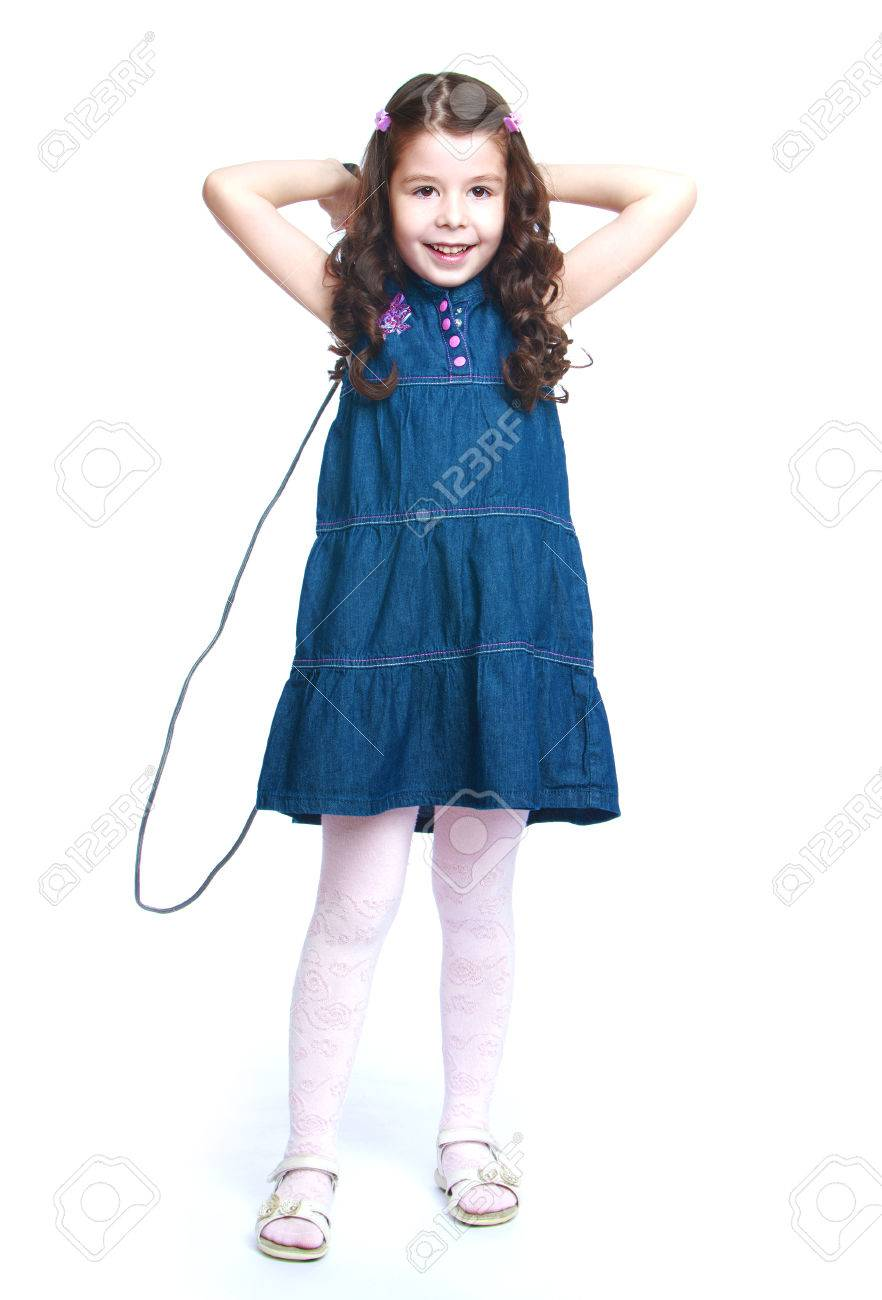 6dee50c0b7f ... white background. Beautiful dark-haired little girl in a long denim  dress jumping rope-Isolated on