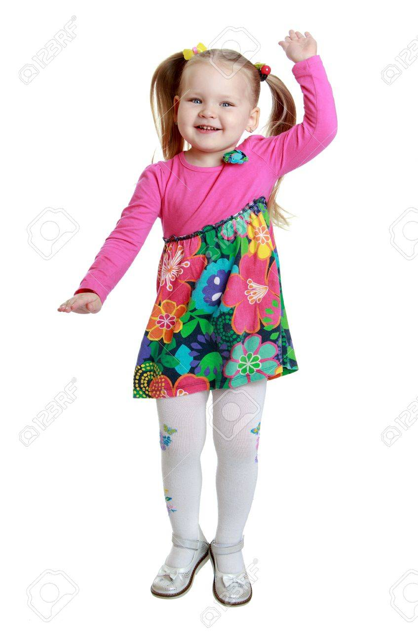 Joyful little chubby girl with braided hair in a ponytail in colorful dress  and white stockings