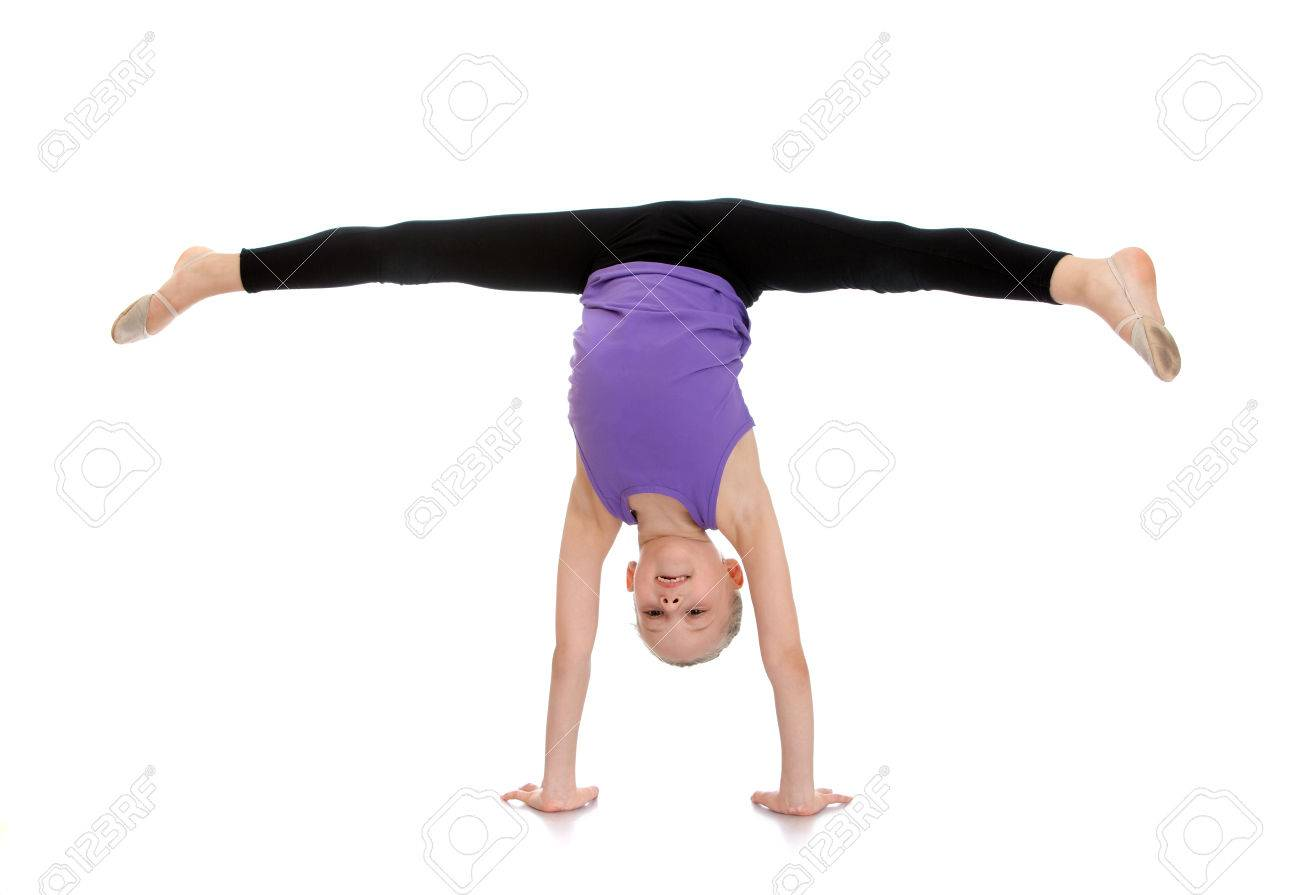 Slim pretty young girl athlete with hair combed into a ball is on your hands and do the splits. - 42931021
