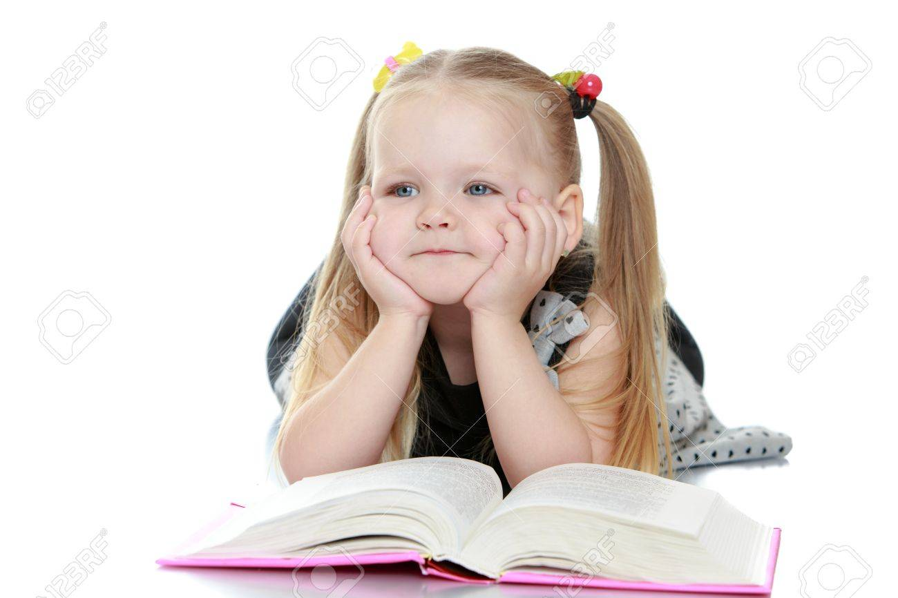 Adorable little chubby,blond girl with long tails on the head lies on the floor leaning on his hands . A girl reads a book and dreams of raising her to the top of the eye-Isolated on white background - 43418323
