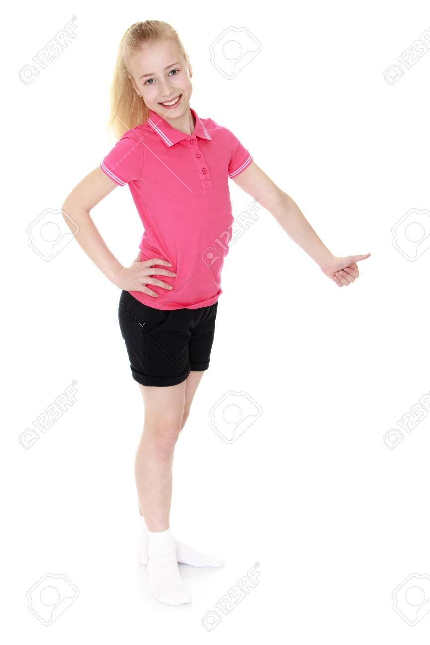 Linda Nina De 12 Anos De Una Cola En La Cabeza En Una Camiseta Rosa Y Pantalones Cortos Negros Cortos Esta De Lado A La Camara Mano Muchacha Muestra El Signo De