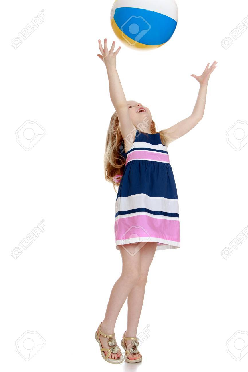 Cheerful little girl in a short summer dress playing with a ball . The girl throws the ball with his hands up-Isolated on white background - 43422210