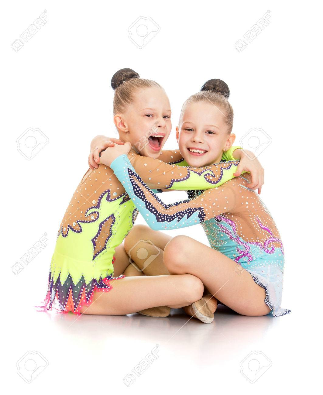 Laughing girls gymnasts sitting on the floor cuddling and fun-Isolated on white background - 43428889