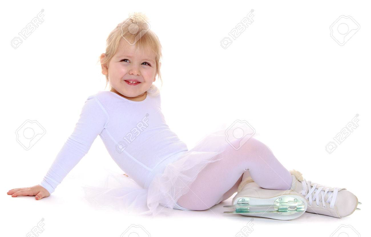 Cute little blonde girl in a white suit for figure skating sits on the floor and smiles. At the feet of the girls are dressed skates for figure skating-Isolated on white background - 43775906